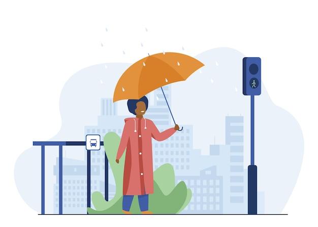 Garçon avec parapluie traversant la route en jour de pluie. ville, piéton, feux de signalisation illustration vectorielle plane. météo et mode de vie urbain