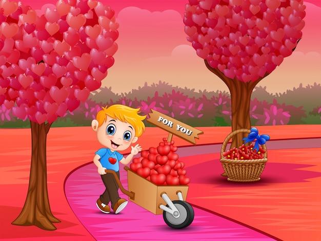 Garçon poussant un tas de coeurs dans un chariot en bois