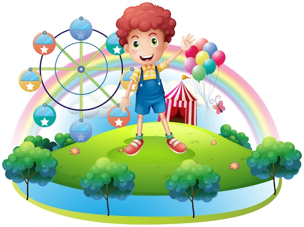 Un garçon près d'un parc d'attractions
