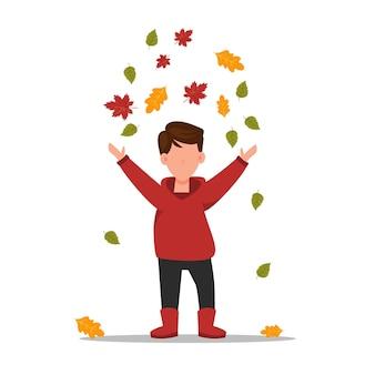 Le garçon rassemble des feuilles l'enfant court par le parc d'automne