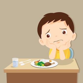 Garçon s'ennuie avec de la nourriture