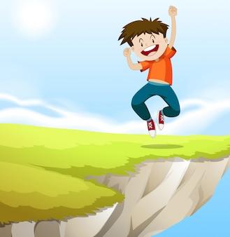 Garçon sautant sur la falaise