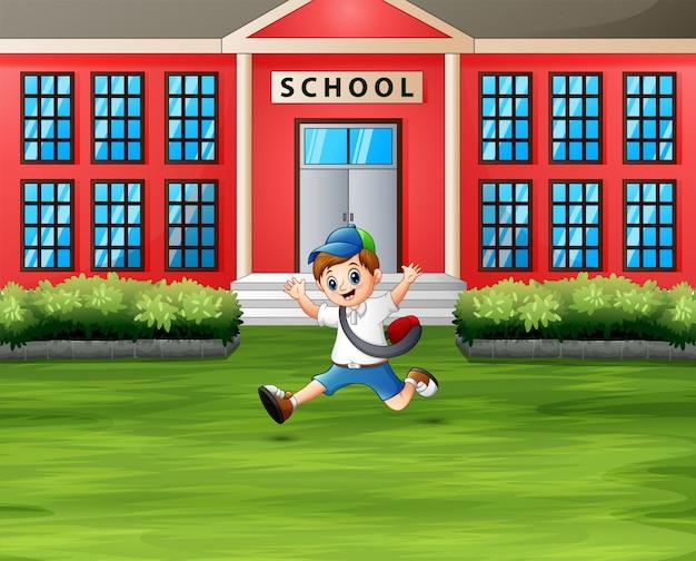 Un garçon saute devant le bâtiment de l'école