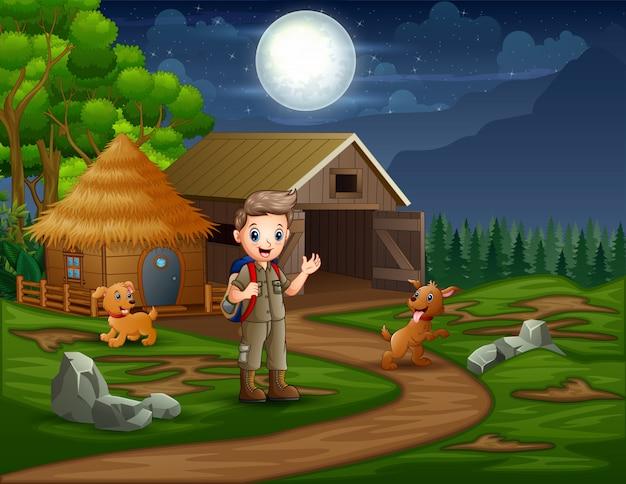 Garçon scout avec des chiens à la ferme