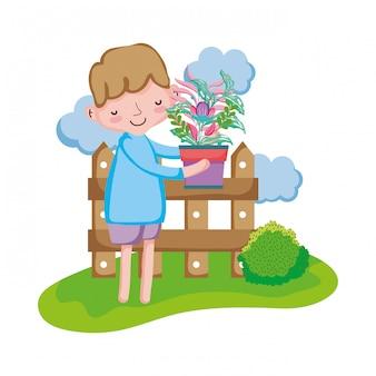 Garçon soulevant une plante d'intérieur avec une clôture dans le paysage
