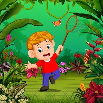 Garçon tente d'attraper un papillon dans la forêt