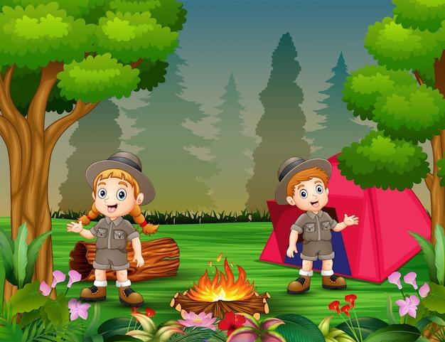 Garçons et filles en tenue de camping près d'un feu de joie et d'une tente