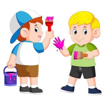 Les garçons jouent avec la peinture violette et le pinceau