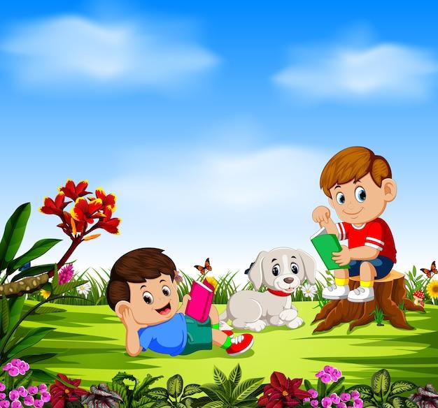 Les garçons lisent la bande dessinée et jouent avec leur chien