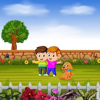 Les garçons marchent avec leur chien dans le jardin