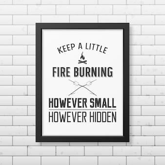 Gardez un peu de feu, aussi petit soit-il caché - citez le fond typographique dans le cadre noir carré réaliste sur le fond du mur de briques.