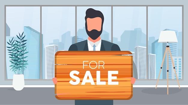 Un gars avec des lunettes tient une pancarte en bois avec l'inscription à vendre. jeune homme tenant une pancarte en bois. le concept de vente d'un appartement, d'un bureau ou d'un immeuble. vecteur.