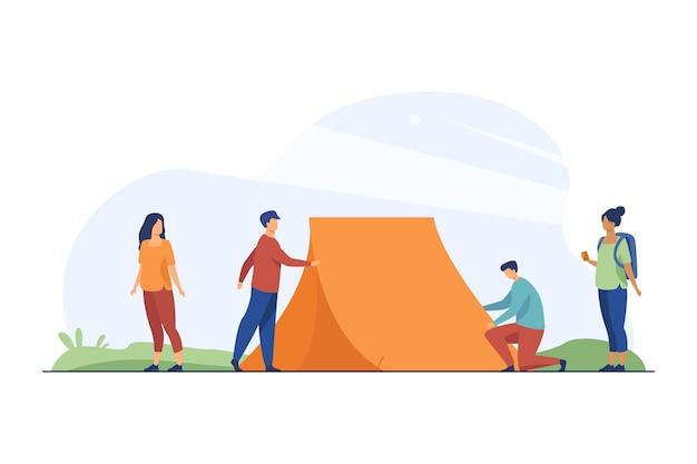 Des gars qui montent une tente sur la nature et des femmes qui regardent