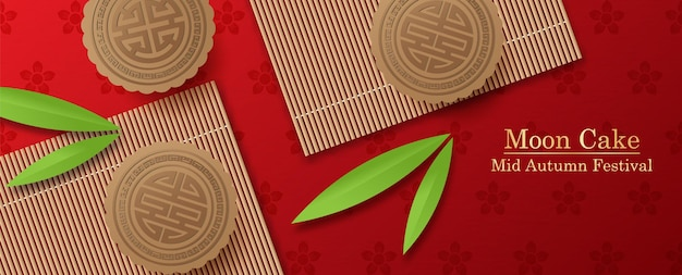 Gâteaux de lune chinois sur des nattes de bambou et des feuilles de bambou sur un motif de fleurs de prunier