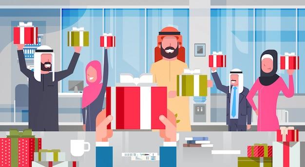 Gens d'affaires arabes chef de groupe donner équipe coffrets présents patron main tenir des cadeaux pour hommes d'affaires musulmans
