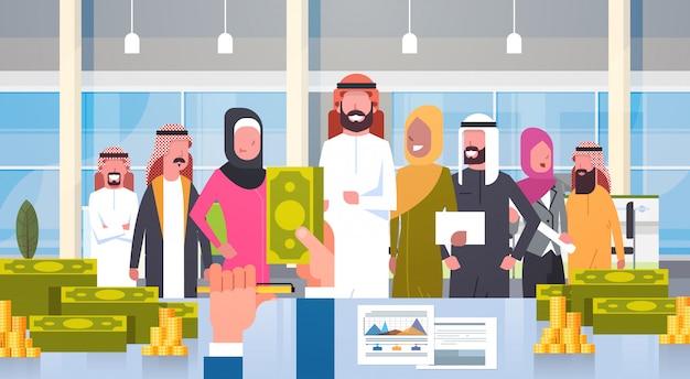 Gens d'affaires arabes dirigeant de groupe donnant salaire en dollar patron main tenant argent hommes d'affaires équipe musulmane
