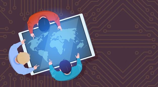 Gens d'affaires assis sur une tablette numérique avec carte du monde en haut, vue de dessus