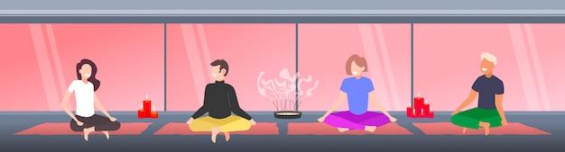 Les gens assis lotus posent des hommes femmes pratiquant le yoga asana pour la méditation des exercices de respiration moderne gymnase studio intérieur pleine longueur horizontale