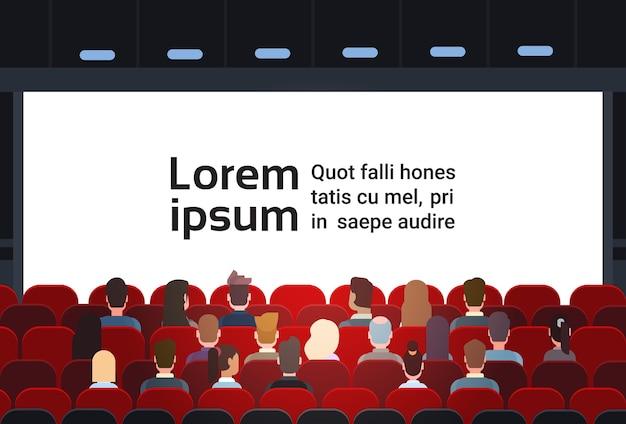 Les gens assoient la salle de cinéma
