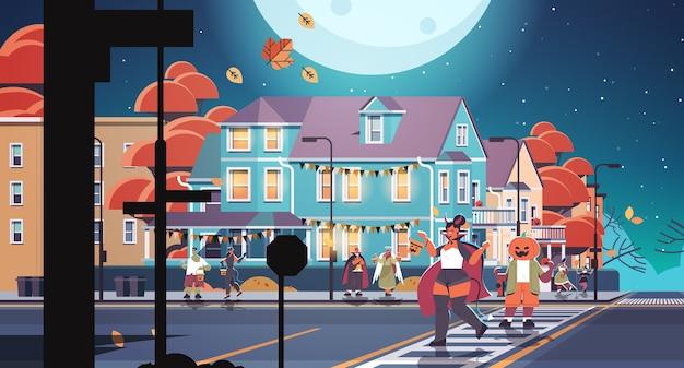 Les gens en costumes marchant dans la ville tromper ou traiter joyeux halloween célébration concept carte de voeux illustration vectorielle pleine longueur horizontale