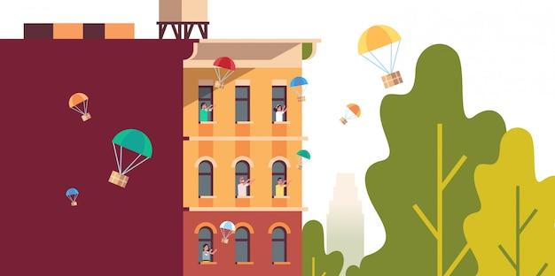 Les gens dans les fenêtres attraper les boîtes à colis tombant avec le parachute du ciel transport expédition air mail express concept de livraison maison moderne bâtiment extérieur portrait horizontal
