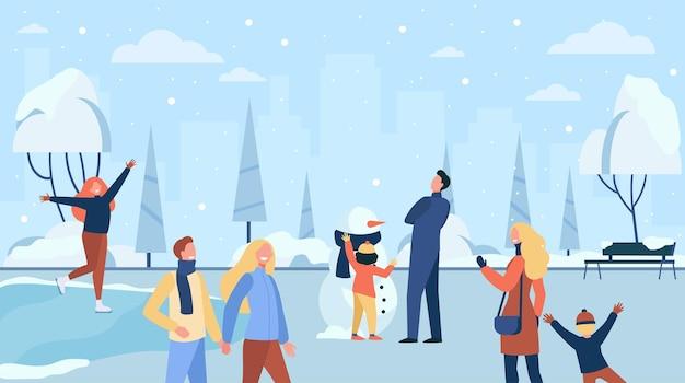 Gens heureux marchant dans le parc d'hiver froid isolé illustration plat. personnages de dessins animés patinage sur glace, jeu et famille faisant bonhomme de neige