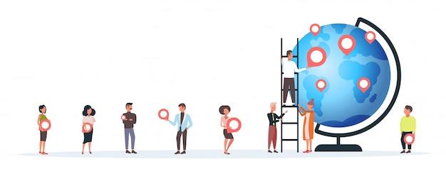 Les gens plaçant des balises géo pointeurs sur globe hommes femmes voyageurs près de la planète terre tenant des marqueurs de localisation gps navigation position commerciale concept de voyage horizontal pleine longueur