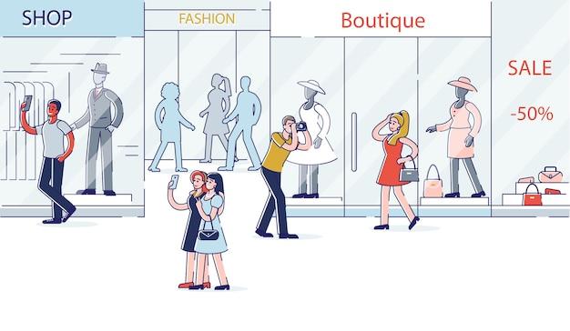 Les gens qui font des photos sur la vitrine de la boutique de mode