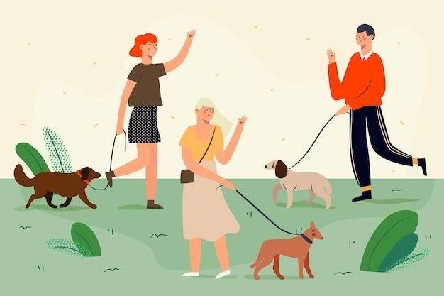 Les gens qui marchent dans le parc avec leurs chiens