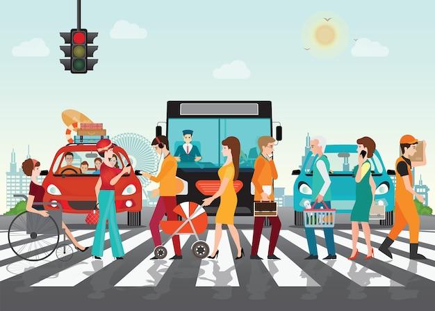 Les gens traversent le chemin de passage sur la route avec des voitures.