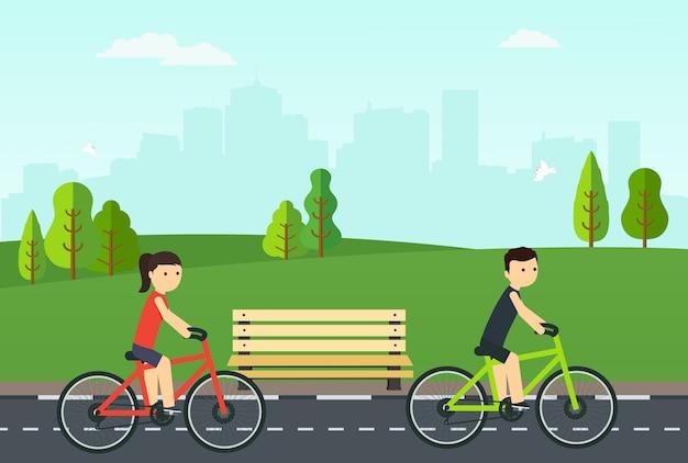 Les gens à vélo roulent dans le parc de la ville.