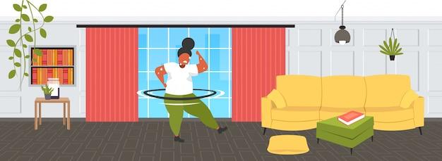 Graisse obèse fille torsion hula hoop surpoids afro-américain sueur femme cardio-training entraînement perte de poids concept pleine longueur moderne salon intérieur horizontal
