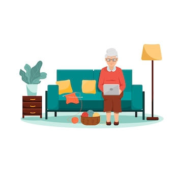 Grand-mère assise sur un canapé avec un ordinateur portable