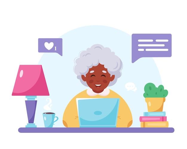Grand-mère assise avec un ordinateur portable vieille femme noire à l'aide d'un ordinateur