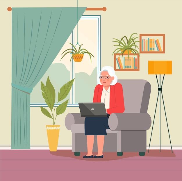 Grand-mère sur un canapé confortable et utilisant un ordinateur portable au salon