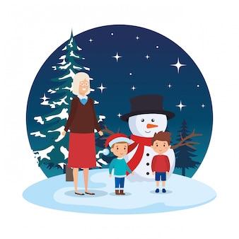 Grand-mère et enfants avec bonhomme de neige dans le paysage de neige