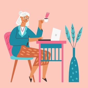 La grand-mère heureuse s'assied au bureau avec l'ordinateur portable
