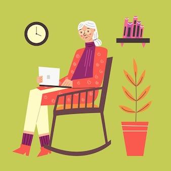 La grand-mère heureuse s'assied dans la chaise berçante avec l'ordinateur portable
