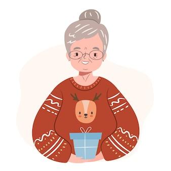 Grand-mère portant un chandail de noël moche une femme âgée heureuse tient un cadeau