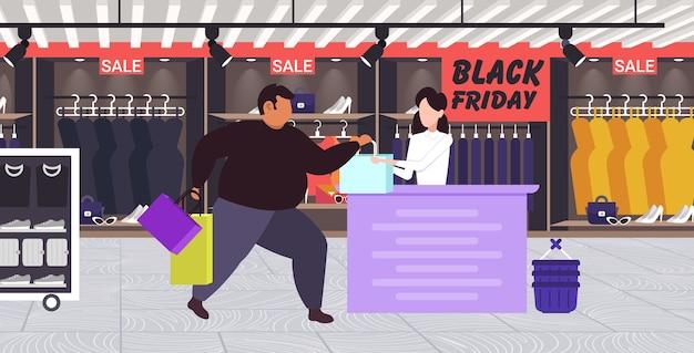 Gros homme acheter des vêtements à la caisse avec femme caissière vendredi noir grande vente