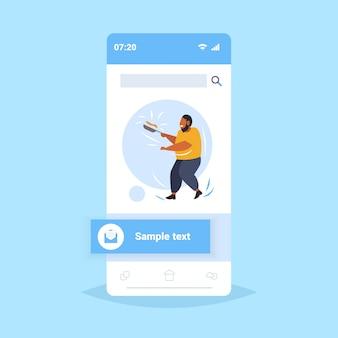Gros homme obèse cuisson des crêpes dans une poêle nutrition malsaine concept de l'obésité en surpoids guy afro-américain préparer le petit déjeuner écran smartphone application mobile en ligne