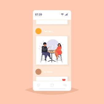 Gros homme obèse femme manger des sushis en surpoids couple afro-américain assis à table en train de déjeuner l'obésité concept de nutrition malsaine écran smartphone application mobile en ligne