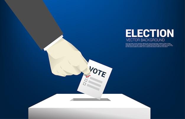 Gros plan main d'homme d'affaires a mis son vote à la case de l'élection.
