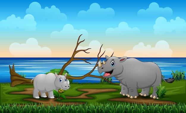 Un gros rhinocéros avec son petit dans le champ