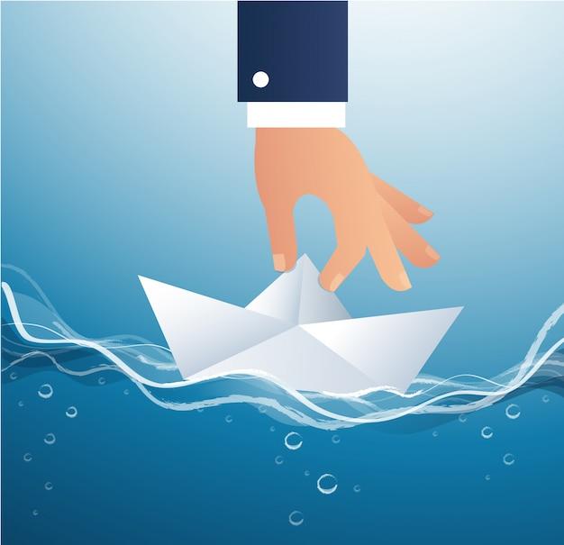 Grosse main tenant le vecteur de bateau en papier