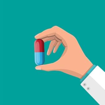 Grosse pilule pour le traitement de la maladie et de la douleur à la main du médecin. médicament médical, vitamine, antibiotique. santé et pharmacie. illustration vectorielle dans un style plat