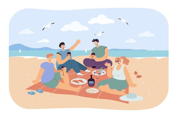 Groupe d'amis heureux en train de pique-niquer sur la plage