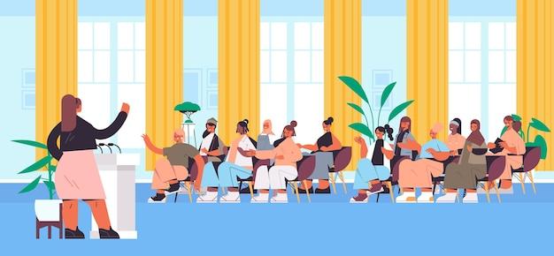 Groupe d'amis de race mixte discutant lors de la réunion dans le club des femmes filles soutenant les uns les autres union des féministes concept amphithéâtre intérieur illustration vectorielle pleine longueur horizontale
