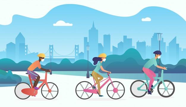 Groupe de cyclistes portant un masque médical de protection et des vélos dans la rue du parc public.