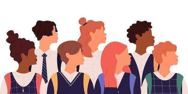 Groupe d'écoliers en uniforme scolaire et sacs à dos de différents groupes ethniques tournés profil
